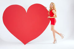 Sexy blonde woman with big heart. Royalty Free Stock Images
