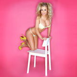 Sexy Blonde Woman In Bikini Kneeling On Chair Stock Photo