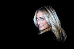 Sexy blonde woman on black background. Beautiful blonde haired woman looking over her shoulder on a black background Royalty Free Stock Image