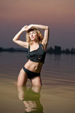 Sexy blonde woman in black lingerie in a river water Stock Photography