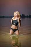 Sexy blonde woman in black lingerie in a river water Royalty Free Stock Images