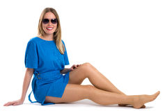Sexy blonde woman in blue dress showing her long legs Royalty Free Stock Photography