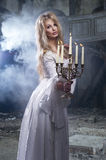 Sexy blonde woman with candelstick Royalty Free Stock Image