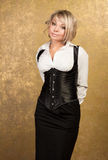 Sexy blonde woman in corset and skirt. On golden background Royalty Free Stock Photography