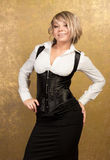Sexy blonde woman in corset and skirt. On golden background Royalty Free Stock Images