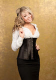 Sexy blonde woman in corset and skirt. On golden background Stock Photography