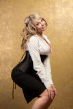 Sexy blonde woman in corset and skirt. On golden background Royalty Free Stock Photos