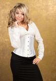 Sexy blonde woman in corset and skirt. On golden background Stock Photo