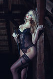 Sexy blonde woman dreaming in barn with whip Stock Photography