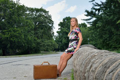 Sexy blonde woman in dress with suitcase Stock Images
