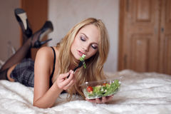 Sexy blonde woman eating salad on bed Royalty Free Stock Images