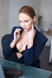 Sexy blonde woman in glasses online flirt in office. Undressing Stock Image