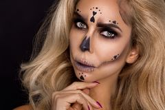 Blonde woman in Halloween makeup and leather outfit on a black background in the studio. Skeleton, monster and witch. Blonde woman model in Halloween makeup and royalty free stock images