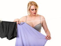 Sexy blonde woman hanging clothes Stock Photography