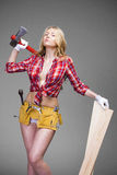 Sexy blonde woman holding an ax and building boards Royalty Free Stock Photos