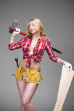 Sexy blonde woman holding an ax and building boards Royalty Free Stock Images