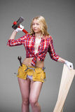 Sexy blonde woman holding an ax and building boards Stock Photography