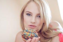 blonde woman holding doughnut Stock Image