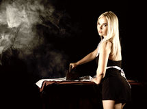 Sexy blonde woman in housekeeper suit, ironing white shirt with old iron. retro style on a dark background Royalty Free Stock Image
