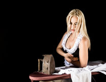 blonde woman in housekeeper suit, ironing white shirt with old iron. retro style on a dark background Royalty Free Stock Images