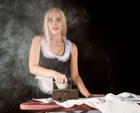 Blonde woman in housekeeper suit, ironing white shirt with old iron. retro style on a dark background. Blonde woman in housekeeper suit, ironing white shirt with stock images