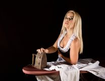 Blonde woman in housekeeper suit, ironing white shirt with old iron. retro style on a dark background. Blonde woman in housekeeper suit, ironing white shirt with stock photo