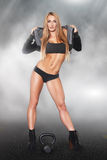 Sexy blonde woman with kettlebell at night Stock Photos