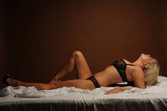 Sexy blonde woman laid on her bed Royalty Free Stock Photography
