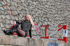 Blonde woman laying on a wall. Beautiful young woman smiling and enjoying the sun in winter time stock photography