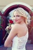 Sexy blonde woman looking back with rose outdoor Royalty Free Stock Photos