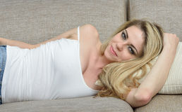 Sexy blonde woman lounges in white tank-top Royalty Free Stock Photography