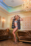 Sexy blonde woman in luxurious  lingerie and elegant fur coat  posing in modern interior. Stock Image