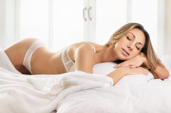 Sexy blonde woman lying on bed Stock Image