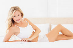 Sexy blonde woman lying on bed smiling at camera Royalty Free Stock Photos