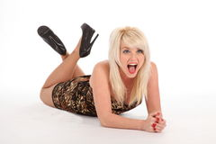Sexy blonde woman lying on floor laughing. Big cheerful laugh from sexy young blonde woman, lying on the floor. Girl is wearing short patterned dress and high Stock Image