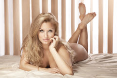 Sexy blonde woman lying naked on bed, looking at camera Stock Photography