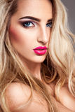 Sexy blonde woman with makeup and blue eyes looking at camera Stock Image