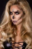 Blonde woman in Halloween makeup and leather outfit on a black background in the studio. Skeleton, monster and witch. Blonde woman model in Halloween makeup and royalty free stock photos