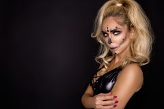 Blonde woman in Halloween makeup and leather outfit on a black background in the studio. Skeleton, monster and witch. Blonde woman model in Halloween makeup and stock images