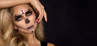 Blonde woman in Halloween makeup and leather outfit on a black background in the studio. Skeleton, monster and witch. Blonde woman model in Halloween makeup and stock photos