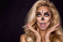 Blonde woman in Halloween makeup and leather outfit on a black background in the studio. Skeleton, monster and witch. Blonde woman model in Halloween makeup and stock photography