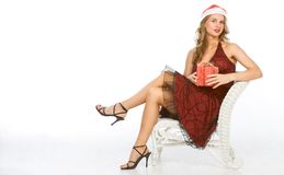 Sexy blonde woman Mrs. Claus with Christmas gift Royalty Free Stock Images