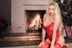 Sexy blonde woman near fireplace lingerie Stock Photo