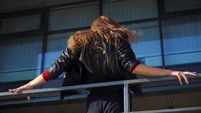Sexy blonde woman performing modern dance near metal railings on city street. Professional dancer in dark clothes dancing in urban environment. people, hobby stock video