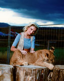 blonde woman playing with lion cub on Royalty Free Stock Images