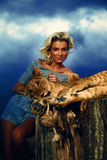 Sexy blonde woman playing with lion cub on Stock Images
