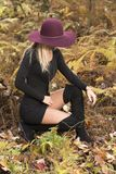Blonde woman poses in black dress and boots. Young blonde woman in stunning black dress and over the knee boots wears a colorful hat in the autumn woods - fall stock photos
