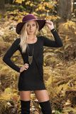 Blonde woman poses in black dress and boots. Young blonde woman in stunning black dress and over the knee boots wears a colorful hat in the autumn woods - fall royalty free stock image