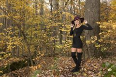 Blonde woman poses in black dress and boots. Young blonde woman in stunning black dress and over the knee boots wears a colorful hat in the autumn woods - fall royalty free stock photo