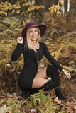Blonde woman poses in black dress and boots. Young blonde woman in stunning black dress and over the knee boots wears a colorful hat in the autumn woods - fall royalty free stock photography